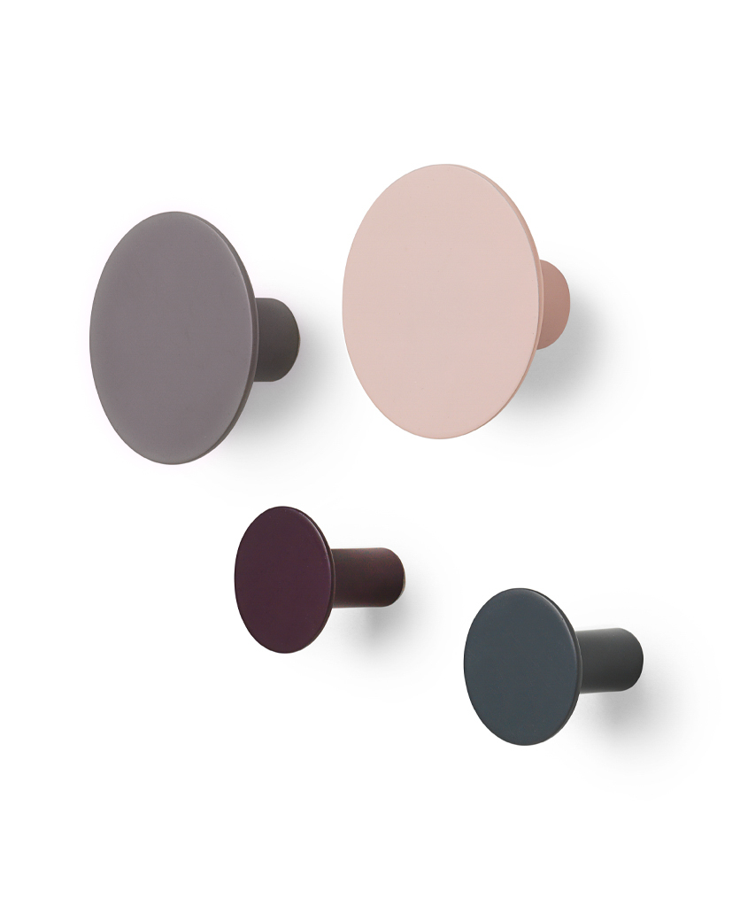four multicoloured circular blomus wall mounted hooks on a white wall