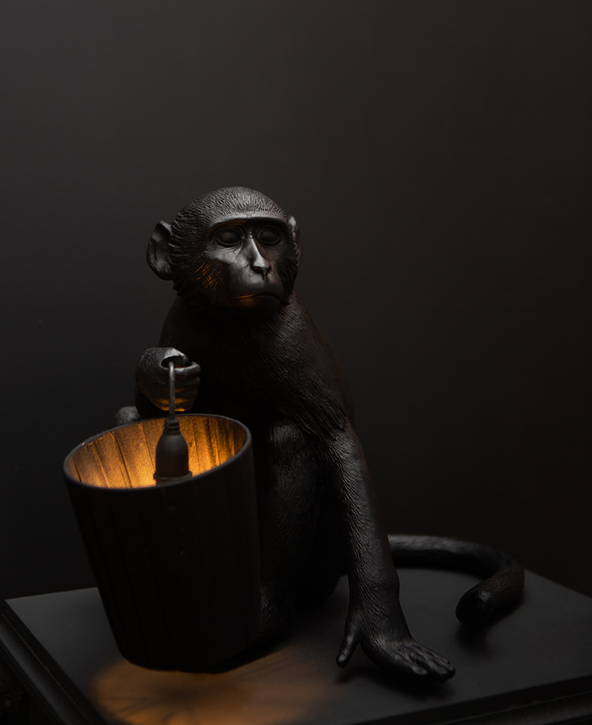 seletti monkey table lamp monkey holding black lamp shade and lit bulb against black background