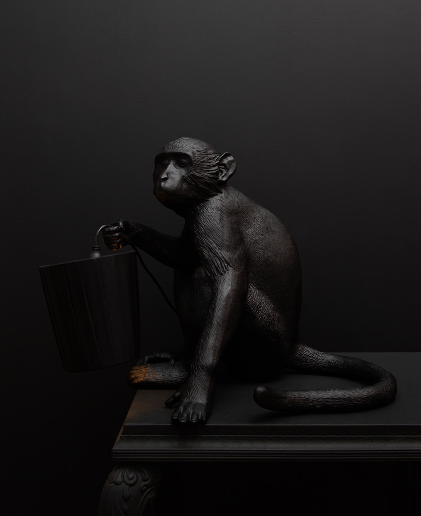 monkey table lamp against a black backdrop