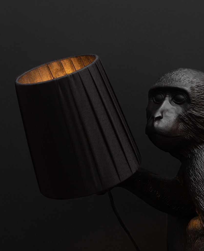 closeup of black lamp shade held in the hand of a monkey table lamp against black background