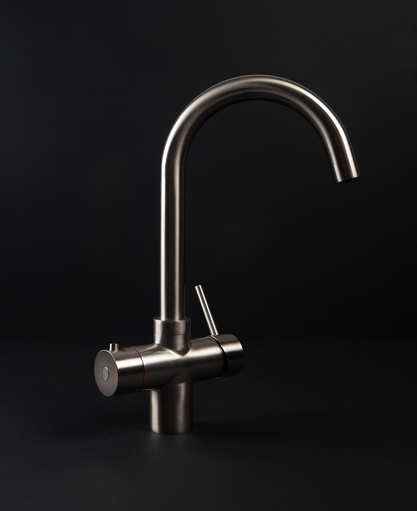 silver hot water tap against black background