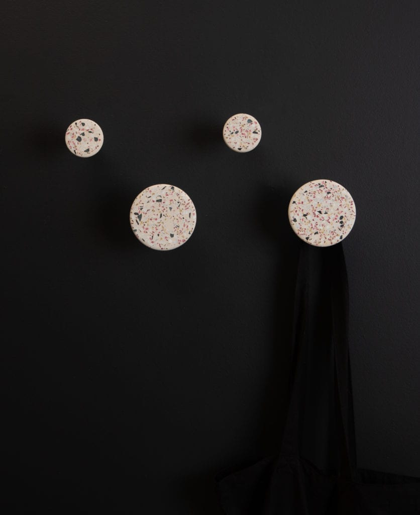 four white terrazzo bloums wall hooks on a black wall