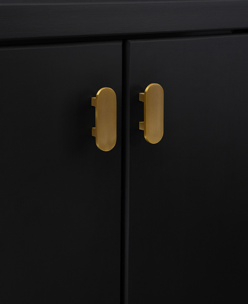 gold metal lozenge shaped kitchen cabinet handles on black cupboard