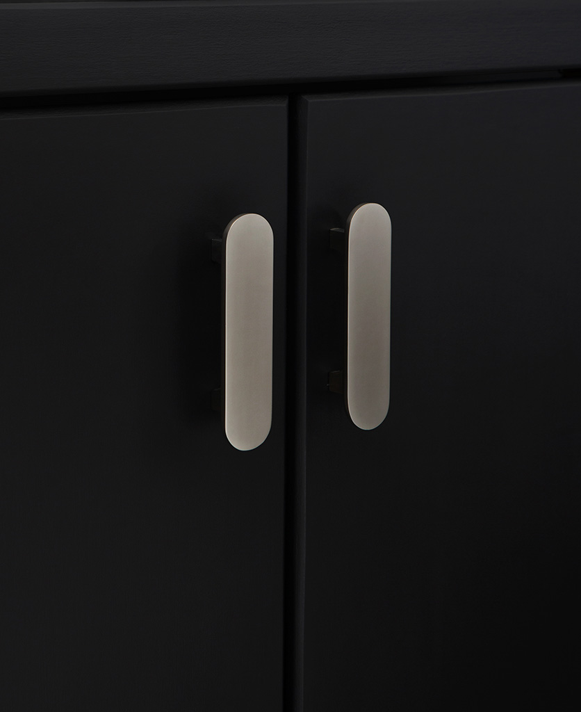 silver lozenge cabinet handle on black cupboards