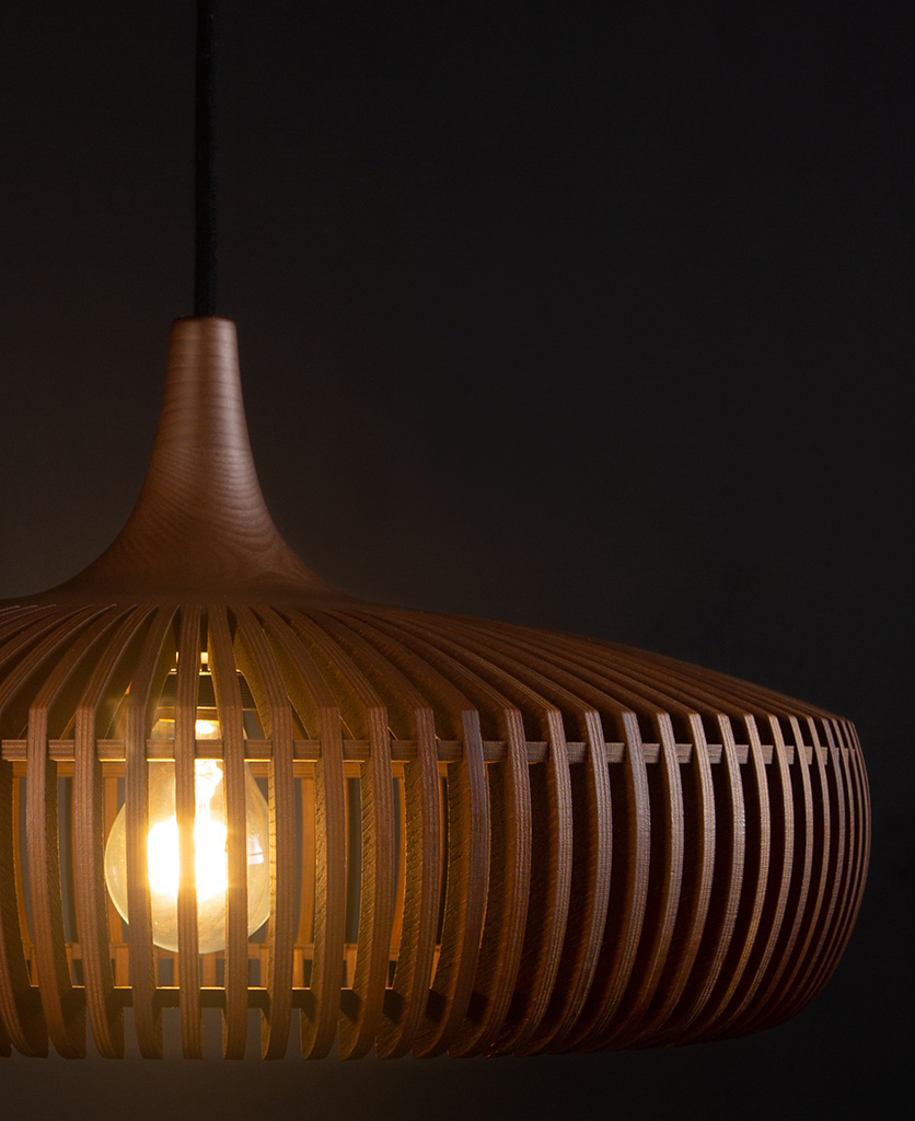 dark oak wooden light shade with black cable close up against black background