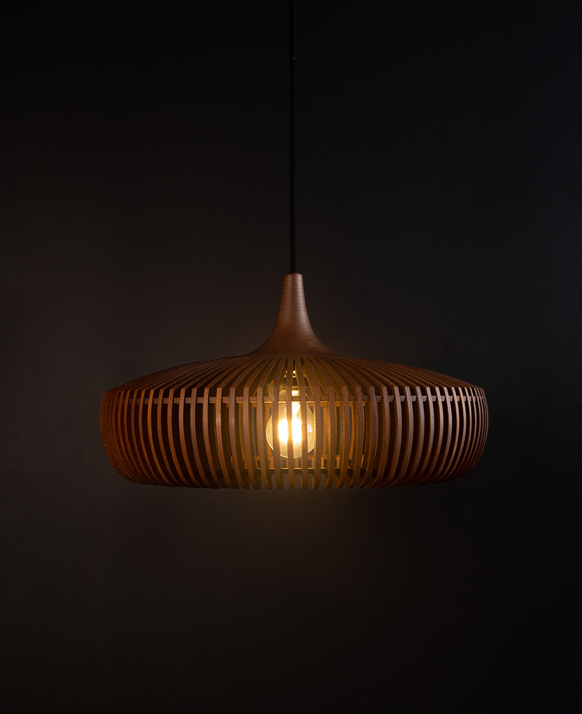 wooden light shade with black cable against black background