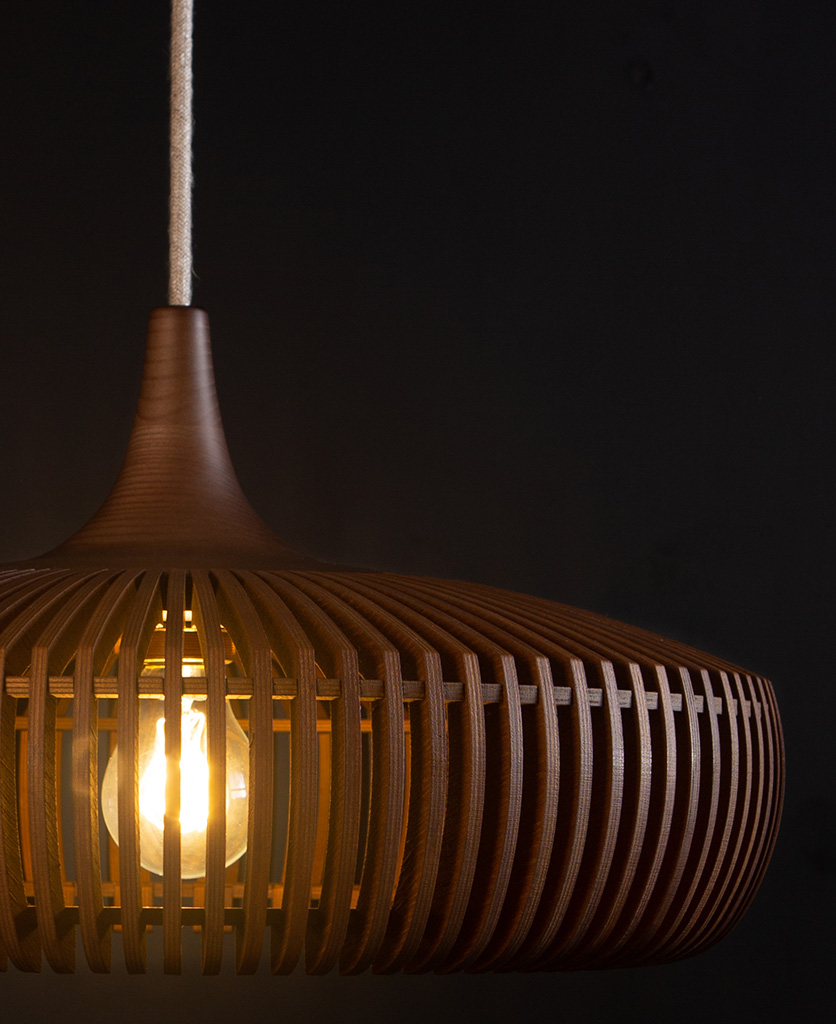 close up of wooden light shade with linen cable against black background