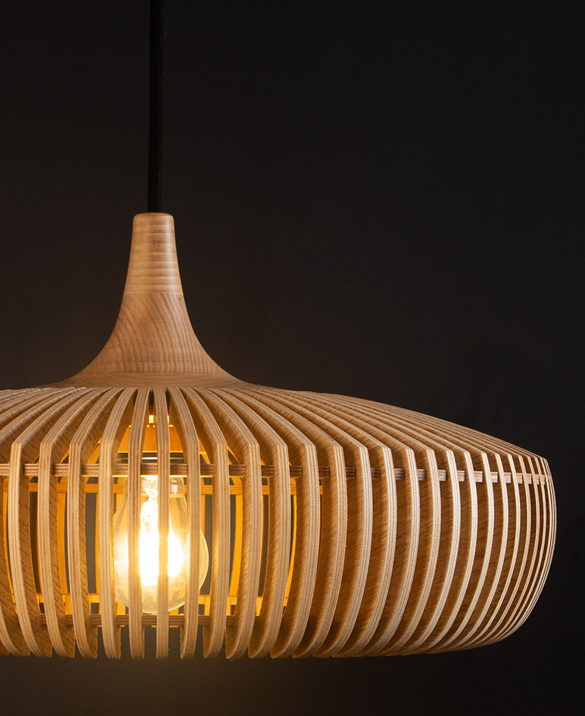 close up of umage clava dine wooden slatted pendant lampshade with black fabric cable against black background