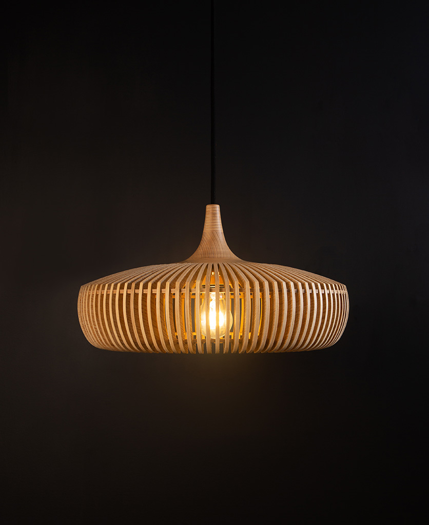 wooden slatted pendant lampshade with black cord against black background