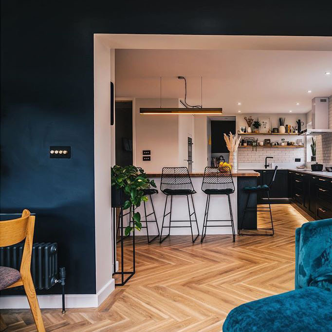 navy and soft pink open plan living-kitchen with wooden floor