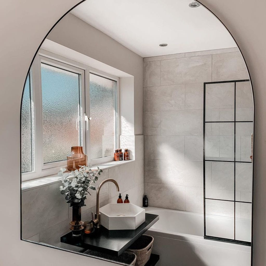 white bathroom with white marbled tiles and black crittal shower screen