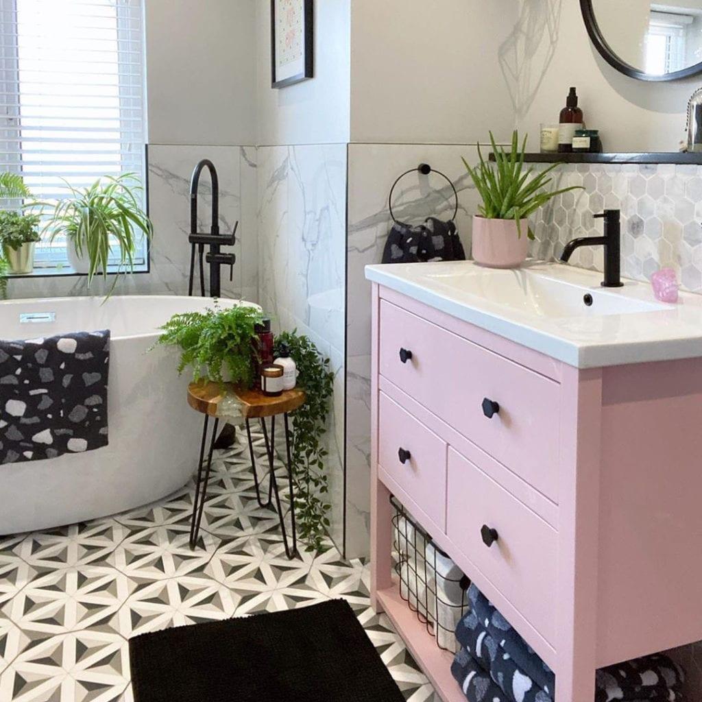 pink cupboard with black bauhaus handles in white marble bathroom