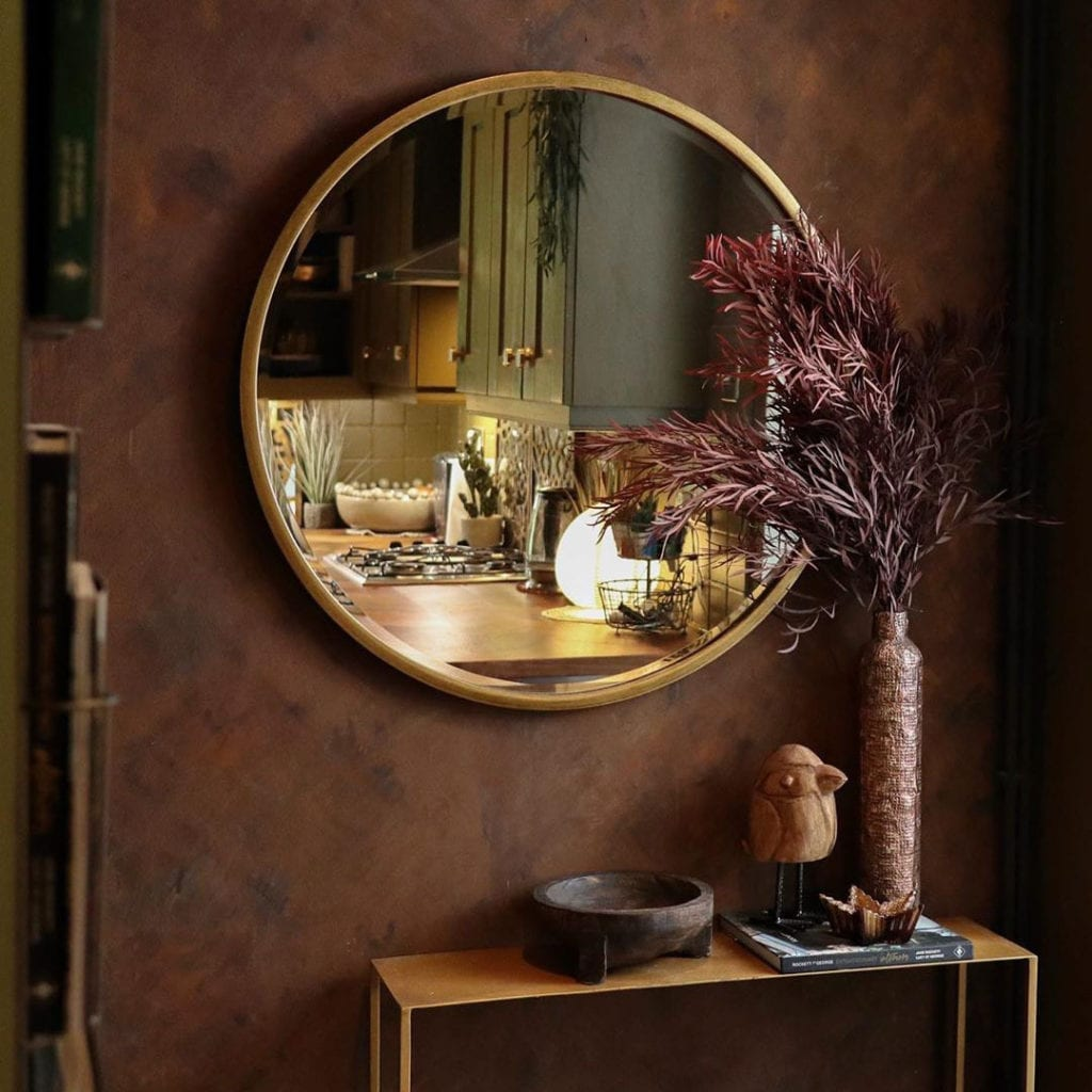 copper effect wall with large gold circular mirror and red eucalyptus nicholli in a copper vase.