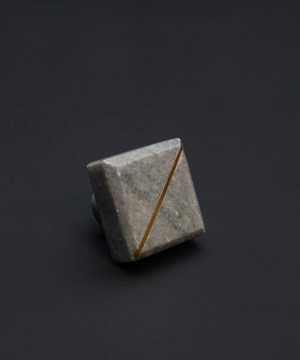 algardi square grey marble knob with gold stripe on black background