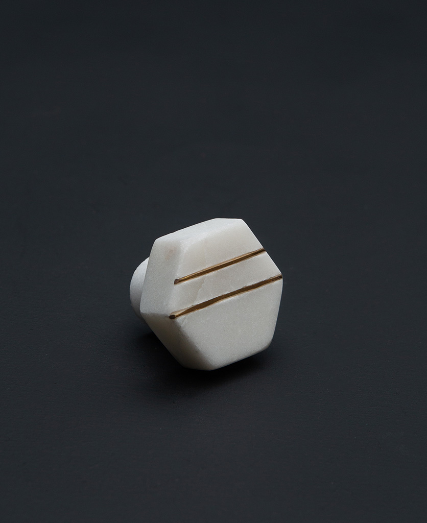 azzolini small white haxagonal marble cabinet knob with two gold stripes on a black background