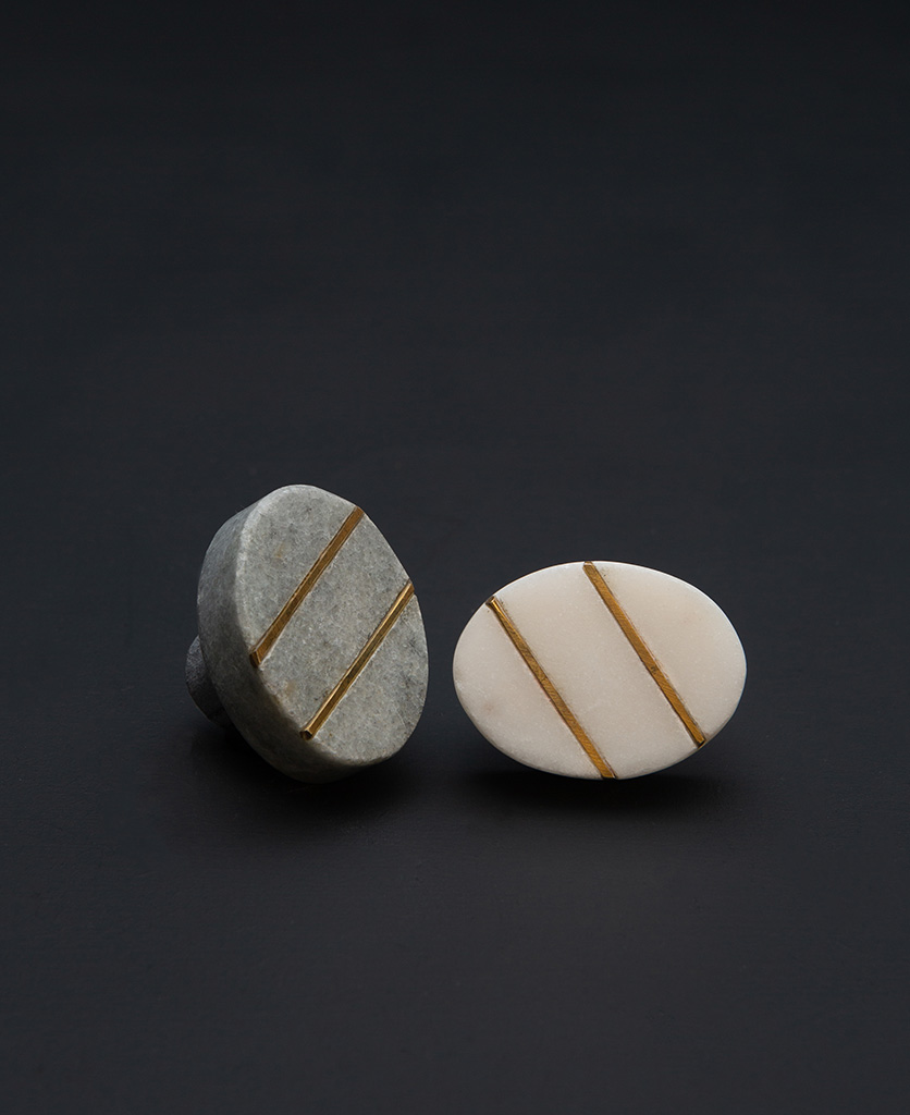one grey and one white oval marble cabinet knobs with gold stripes on black background