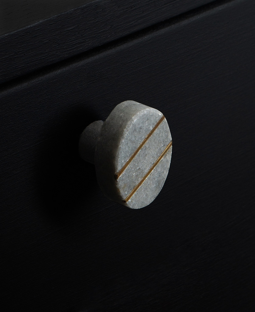 barruzi grey oval marble knob wit two gold stripes on black drawer