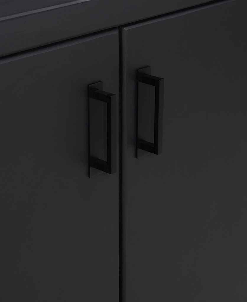 12.7cms black metal handle with back plate attached to black cupboard