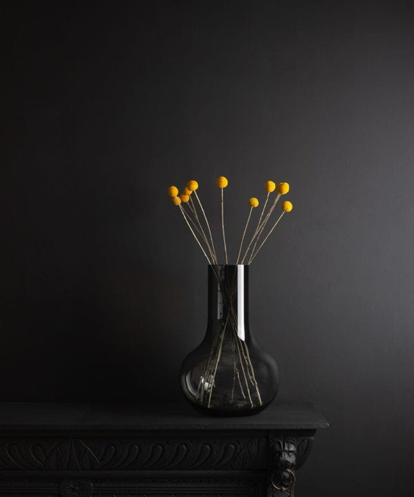 bowl vase with dried yellow craspedia stems on black background