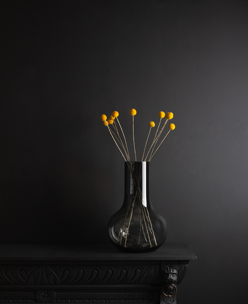 bowl vase with dried yellow craspedia stems against black background