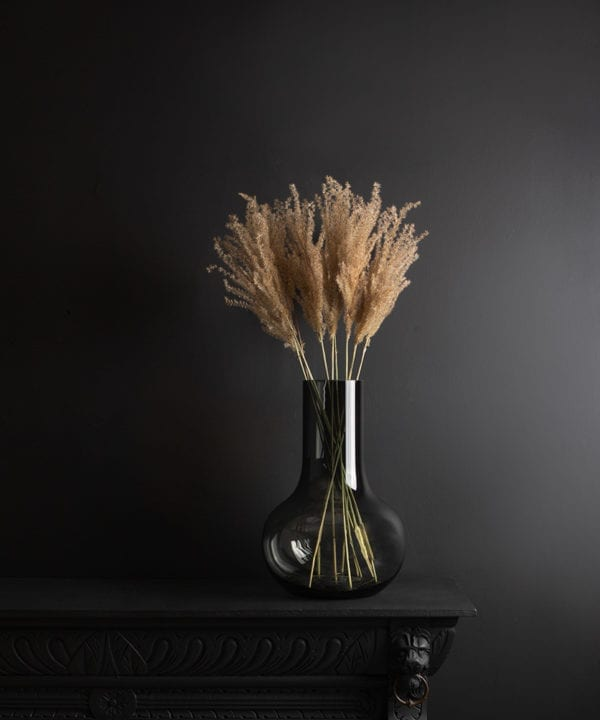 bowl vase with dried fluffy reed grass bouquet against black background