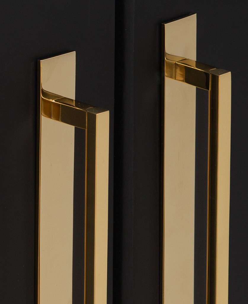 close up of metal handles in gold fixed to a black cupboard