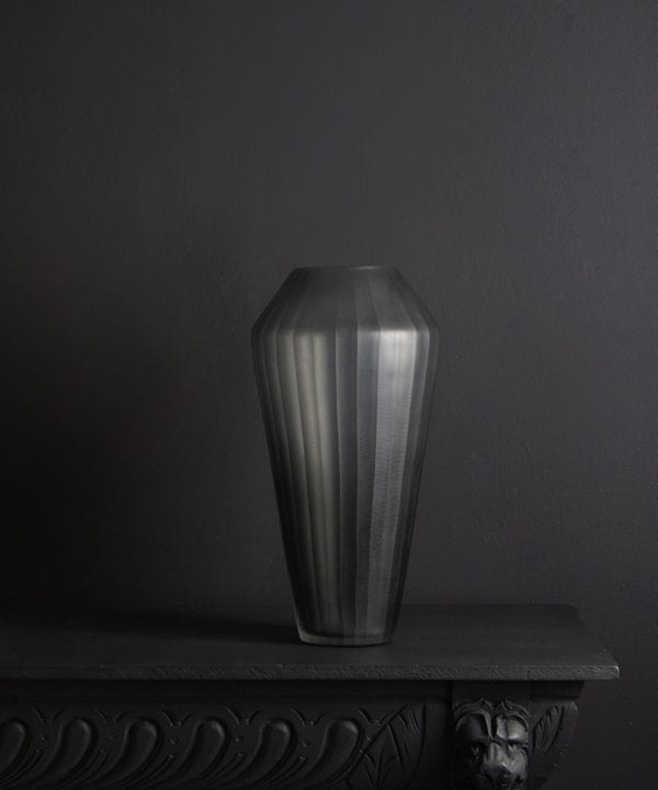grey ribbed vase against black background