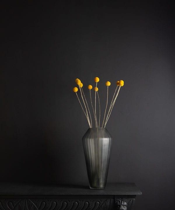 grey vase with yellow craspedia bouquet against black background