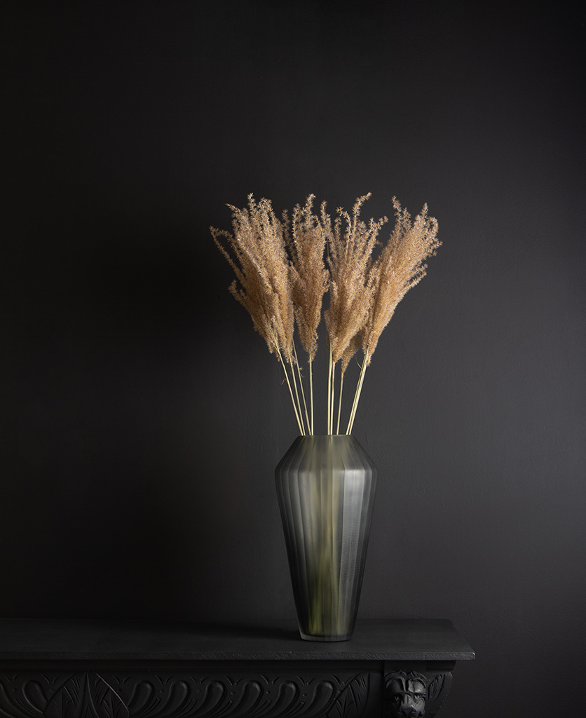 grey vase with fluffy reed grass bouquet against black background