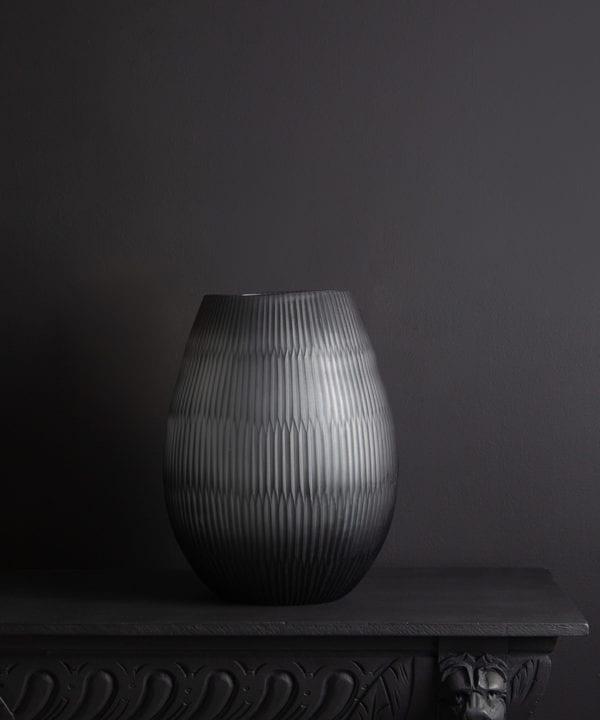 tall textured glass vase against black background