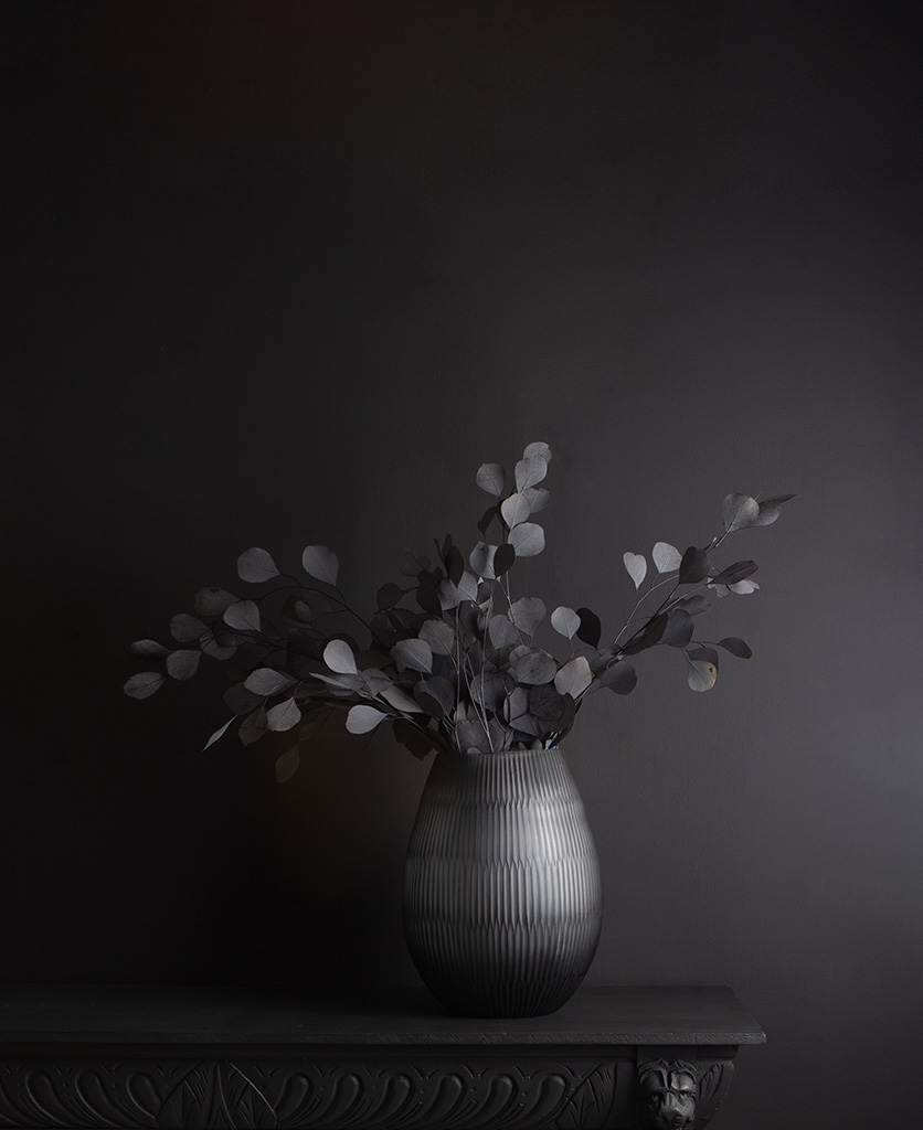 tall glass vase with preserved eucalyptus bouquet against black background