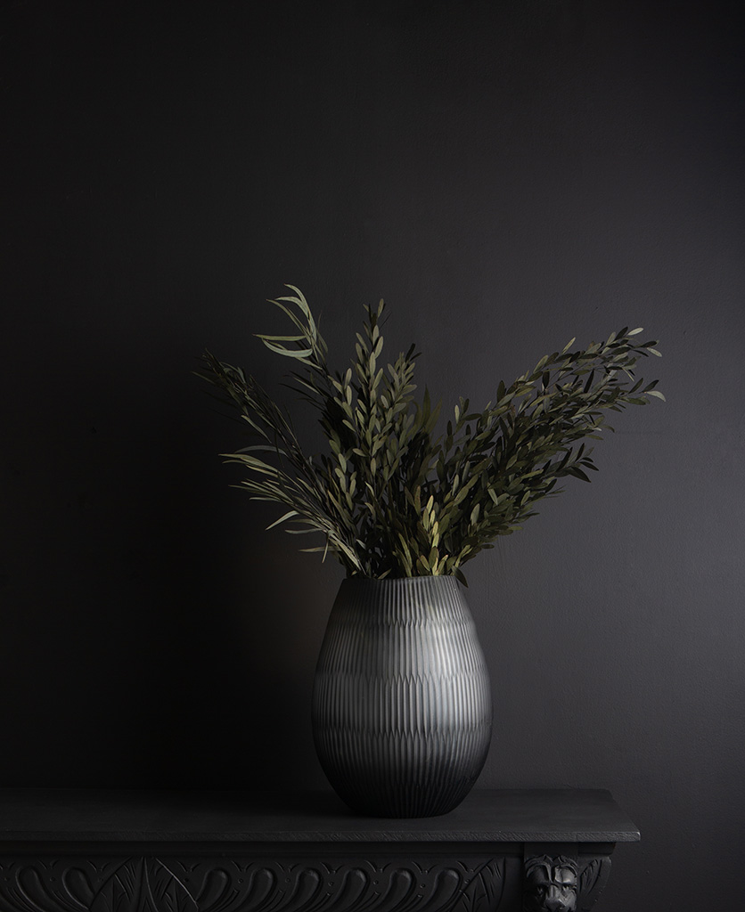 tall glass vase with preserved green nicholii bouquet against black background