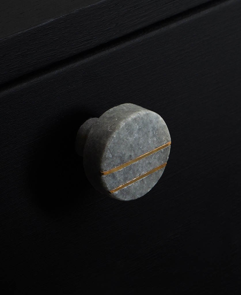 Marini round grey marble knob with two gold stripes on black drawer