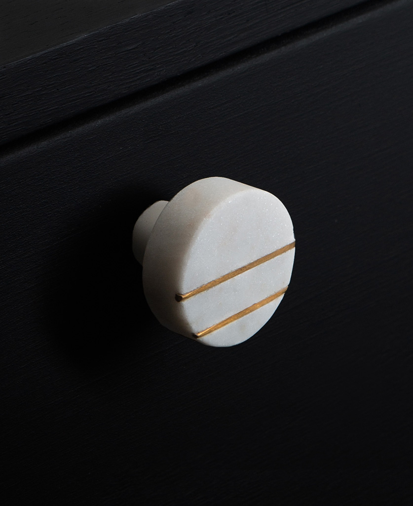 marini round white marble knob with two gold stripes on black drawer