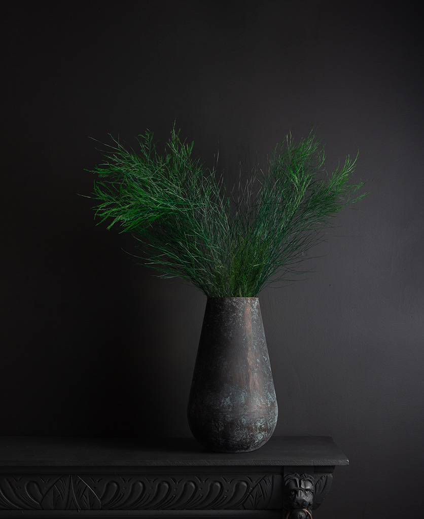metal vase with preserved asparagus tree fern bouquet against black background