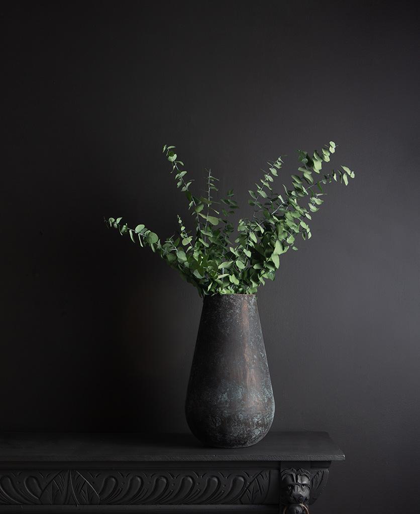 metal vase with preserved eucalyptus stuartiana bouquet against black background