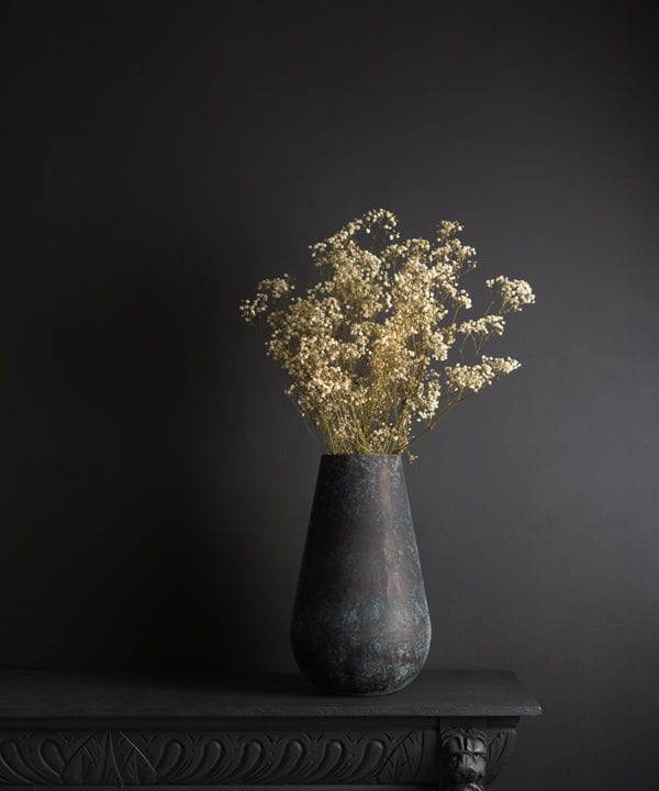 metal vase with preserved gypsophila bouquet against blck bckground
