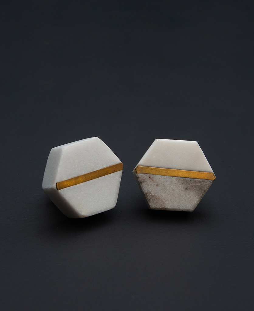 hexagonal white marble kitchen knobs with contrasting brass inlay and grey hexagonal marble drawer knobs with gold stripe on black background