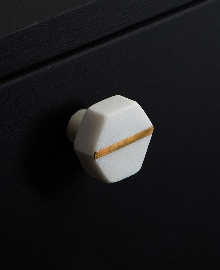 White hexagonal marble knob with brass stripe on black cupboard