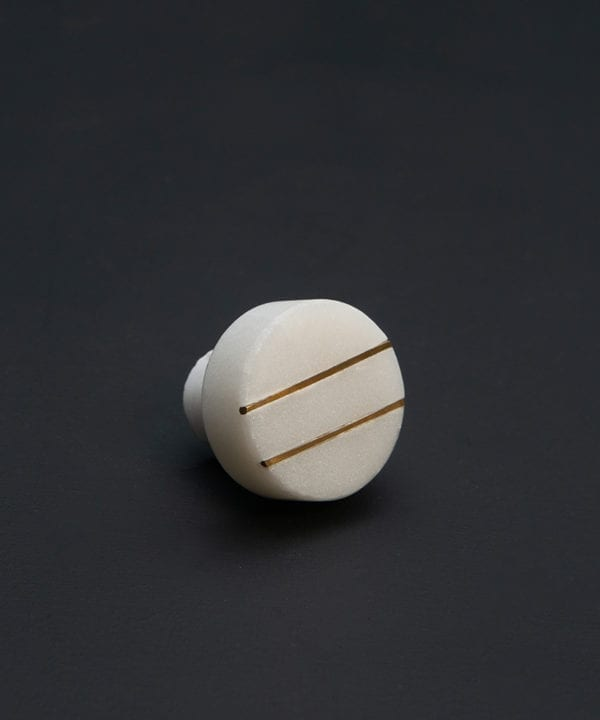 romanelli round gold and white marble knob with brass stripes on black background
