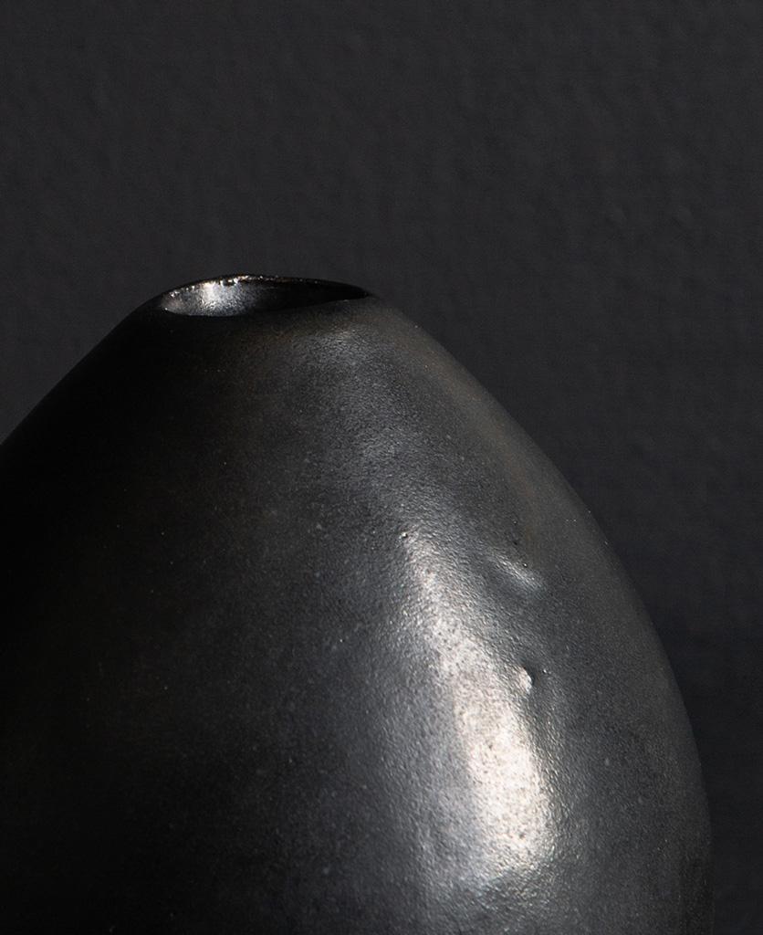 close up of black stem vase against black background
