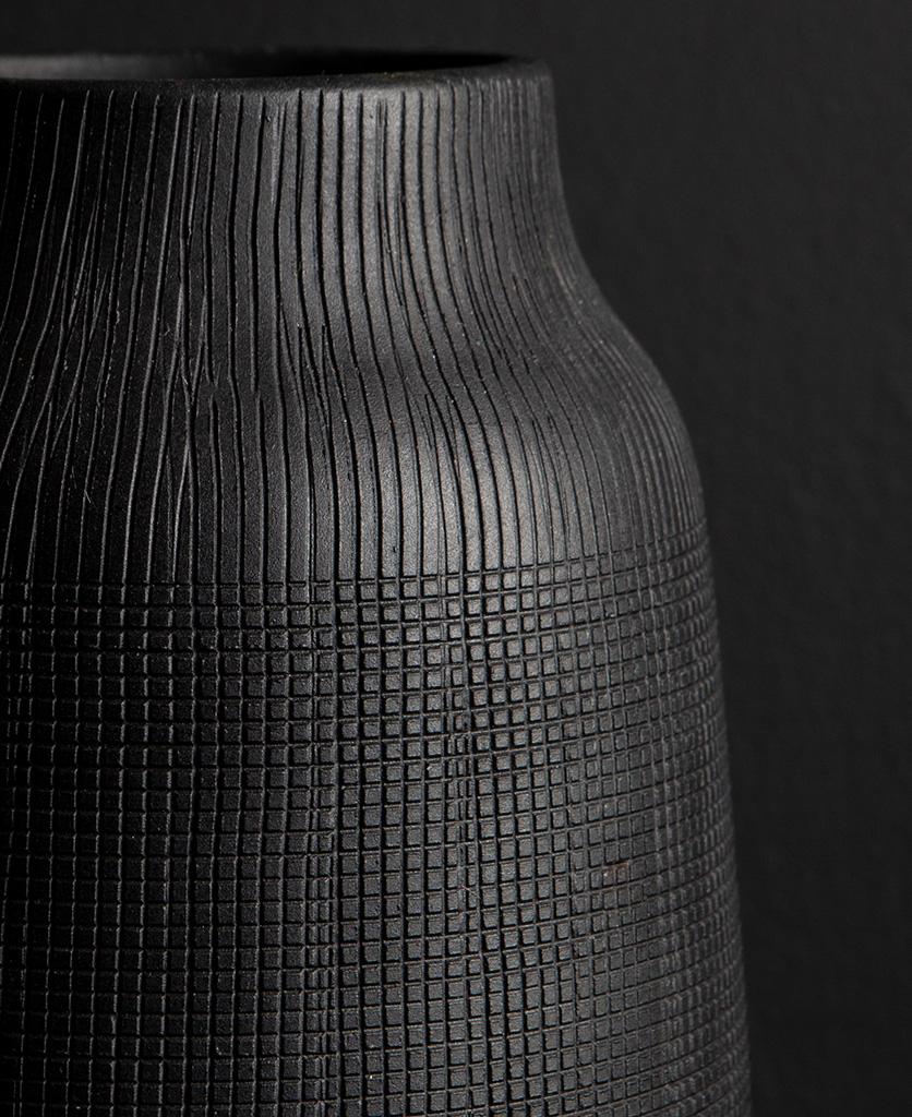 close up of black vase against black background
