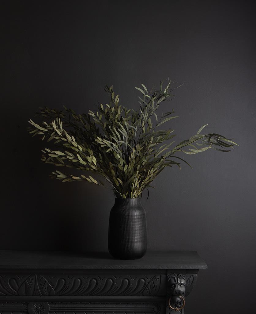 black vase with preserved green nicholii bouquet against black background