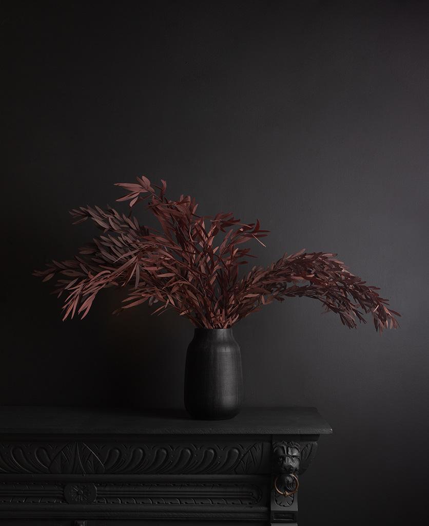 black vase with preserved red nicholii bouquet against black background