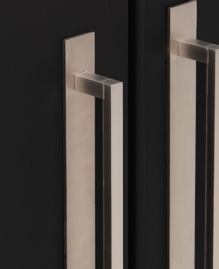 close up of silver metal handles on black cupboard doors