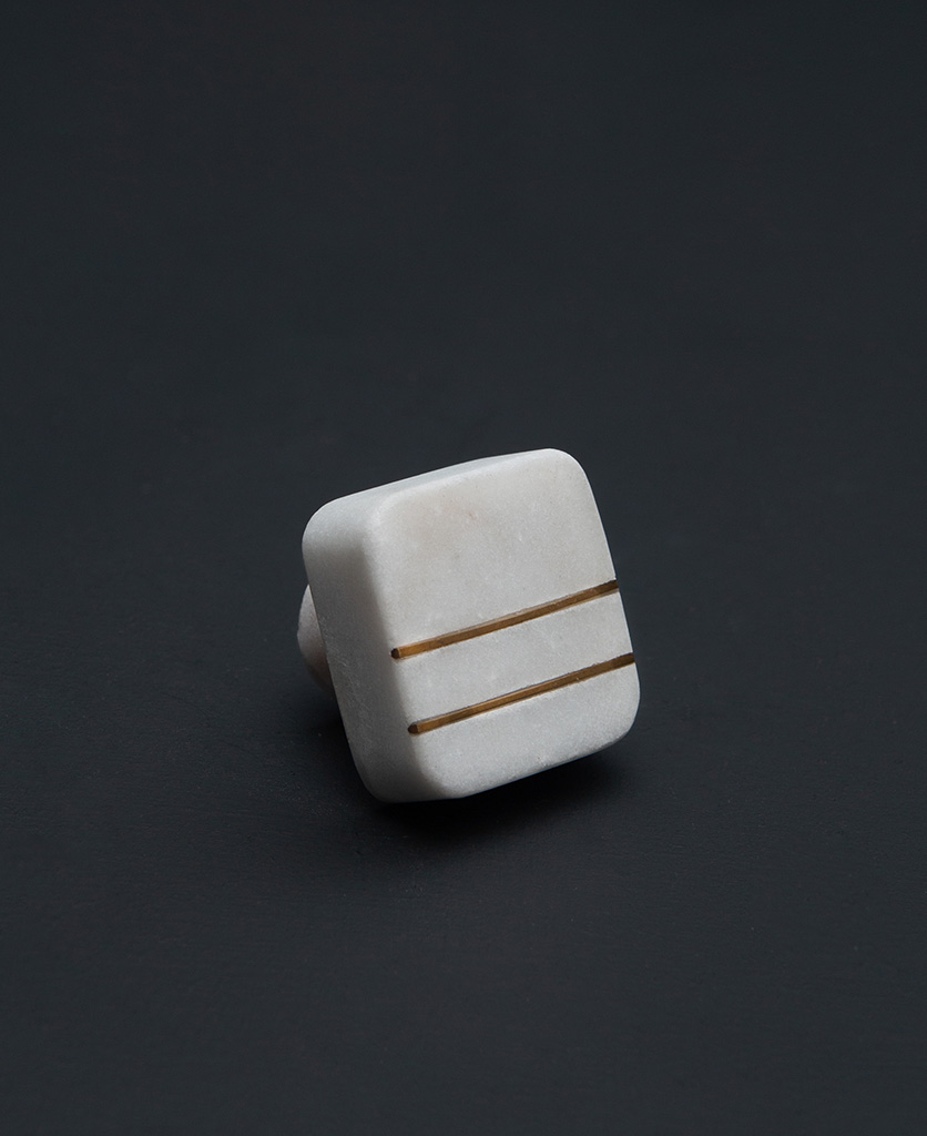 white square marble knob with two brass stripes on black background