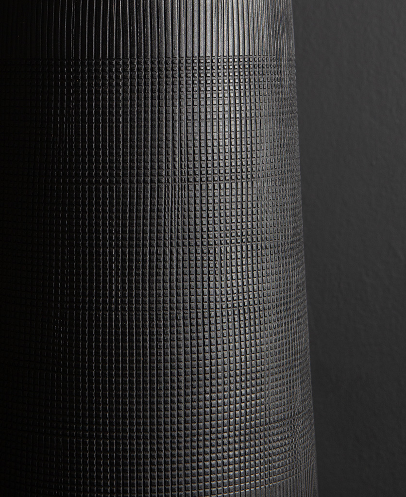 close up of black tall vase against black background