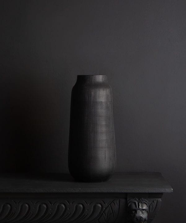 black tall vase against black background