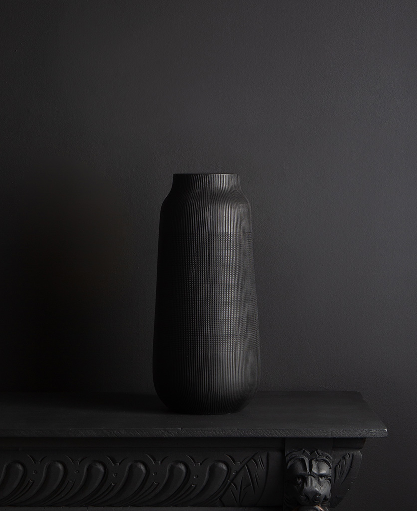 black tall vase against black background