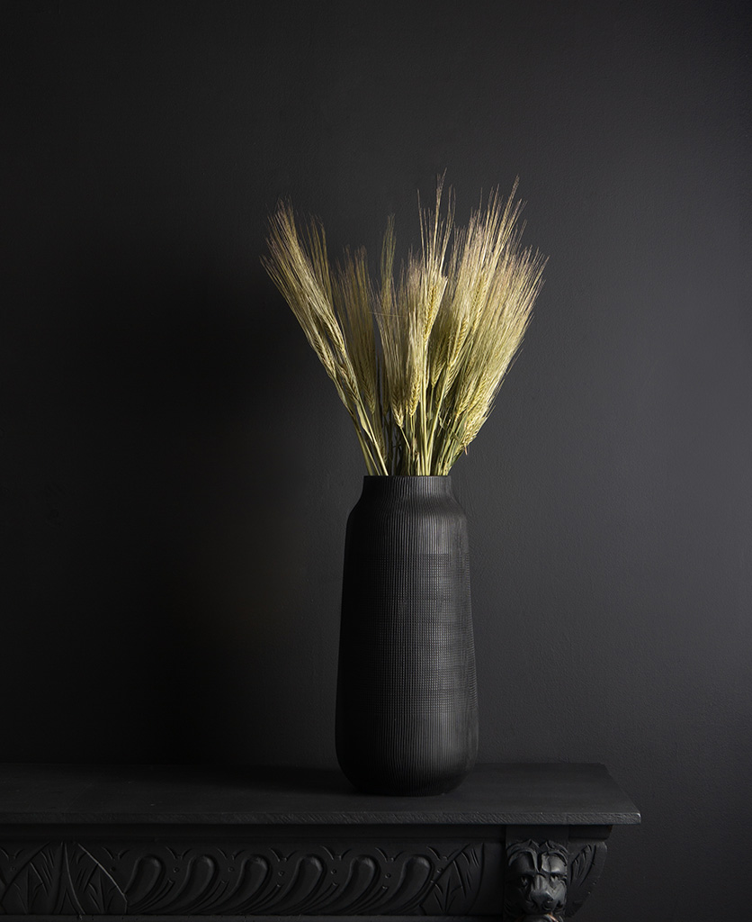 black tall vase with preserved barley bouquet against black background